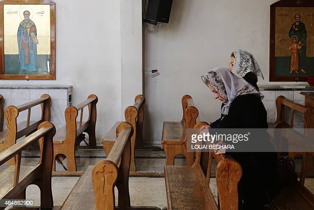 Displaced Assyrians who had fled their hometowns due to Islamic State Group attacks against their communities take part in a prayer at the Ibrahimal...