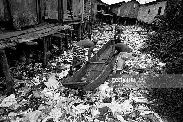 Displaced boys push the canoe over the garbage patch in the stilt house area in Tumaco, Nariño dept., Colombia, 18 June 2010. With nearly fifty years...