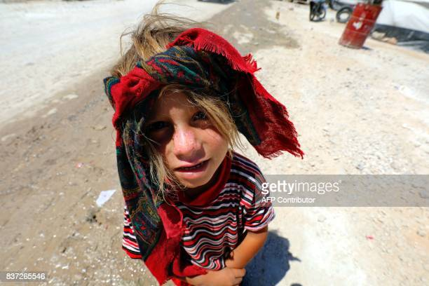 Displaced child from the Islamic State group's Syrian stronghold of Raqa, poses for a photo at a camp in Ain Issa on August 22, 2017. / AFP PHOTO /...