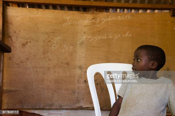 A displaced child sits next to a board during a class at the IDP camp at Bangassou in the southeast of the Central African Republic on June 11 2018...