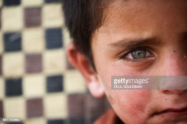 A displaced child who fled from the Islamic State group bastion of Raqa looks on in a camp for displaced near the town of alKaramah 26 kms from Raqa...
