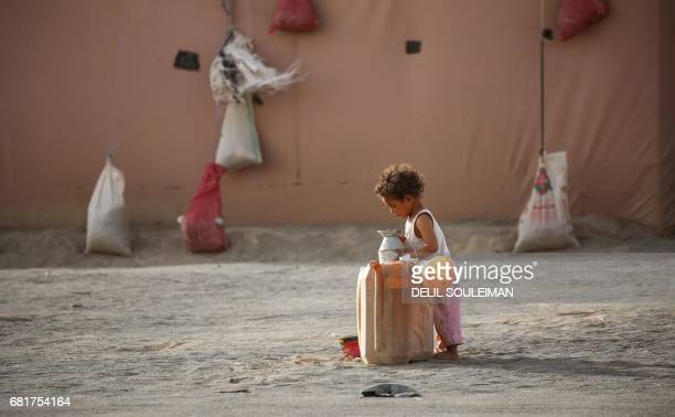 Displaced child, who fled from the Islamic State group bastion of Raqa, walks holds a metallic jug next to a jerrycan in a camp for displaced near...