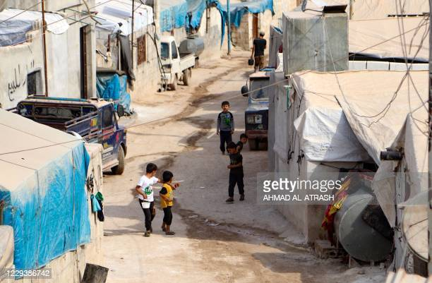 Displaced children gather in one of the alleys of an overcrowded displacement camp near the village of Qah near the Turkish border in Syria's...