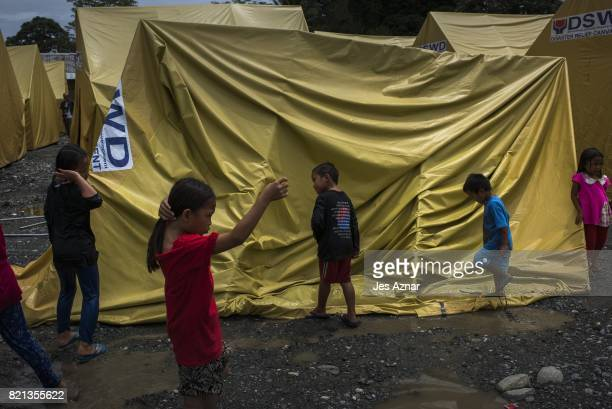 Displaced children playing on a damaged tent inside a makeshift evacuation center on July 23 2017 in Pantar Lanao del Norte southern Philippines...