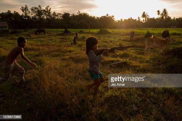 Displaced children playing with wooden toy guns inside a temporary shelter area in Mamasapano Maguindanao on August 22 in Mamasapano Maguindanao...