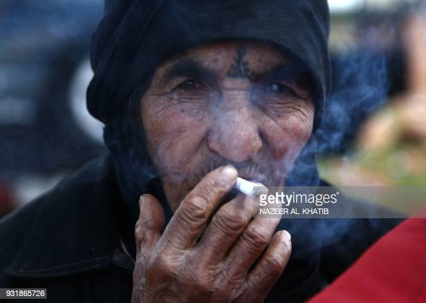 A displaced civilian from the Kurdishmajority city of Afrin in northern Syria which is nearly surrounded by Turkishled forces smokes a cigarette...