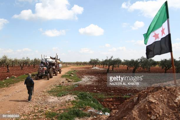 Displaced civilians from the Kurdishmajority city of Afrin in northern Syria which is nearly surrounded by Turkishled forces arrive in the village of...