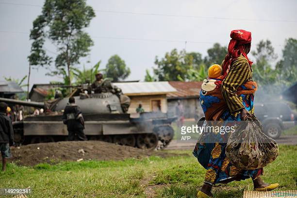 Displaced Congolese lady and her child walk past a retreating government army tank in the village of Rugari, around 37km from Goma, following an...
