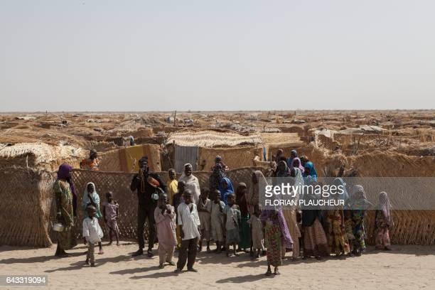 Displaced families stand at the main gate of a camp for internally displaced people at Monguno district of Borno State on February 14 2017 The...