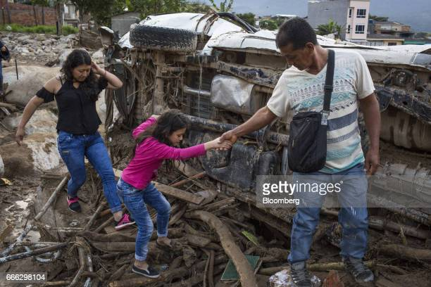 A displaced family walks through debris after a landslide in the San Miguel neighborhood of Mocoa Putumayo Colombia on Monday April 3 2017 Torrential...
