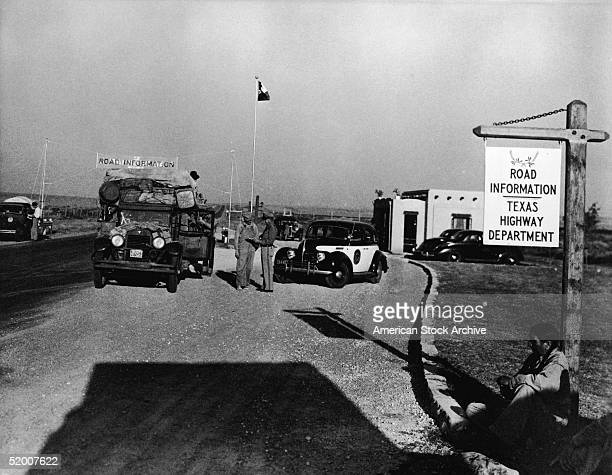 Displaced farm workers from Oklahoma referred to as Okies stop at Road Information on the Texas state border as they flee the Dust Bowl Texas 1930s A...
