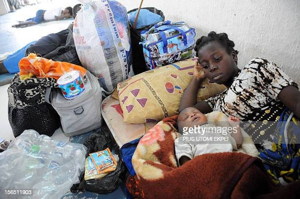 Displaced flood victim 15yearold mother Gladys Marcus looks at her twoweekold child delivered in a relief camp waits to be evacuated following...