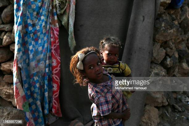 Displaced girl who fled her home due to the war carries her little brother at a camp on July 22, 2019 in the outskirts of Sana'a, Yemen. As a result...