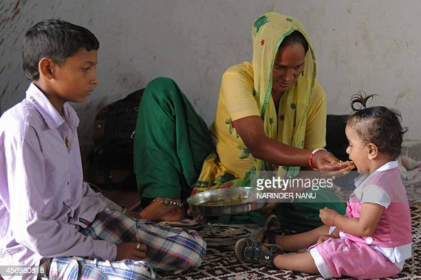 A displaced Indian villager who fled firing along the IndiaPakistan border feeds her child at a relief camp in R S Pura about 20 kms from Jammu on...