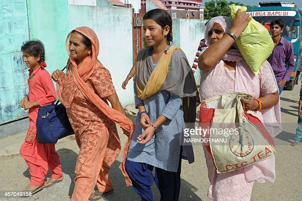 Displaced Indian villagers who fled their residences following crossborder firing between Indian and Pakistan troops arrive in their village to feed...