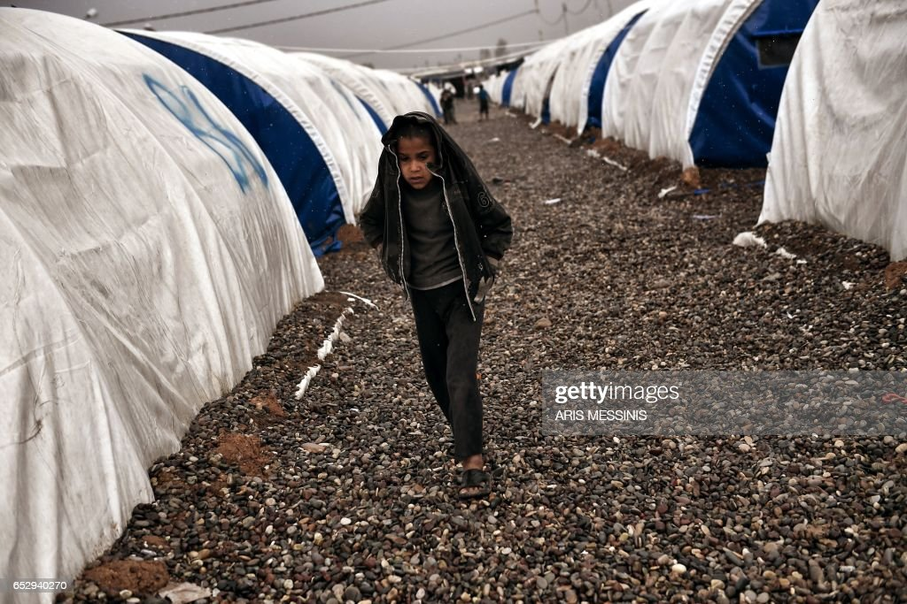 A displaced Iraqi boy from Mosul walks under the rain at the Hamam al-Alil camp on March 13, 2017, during the government forces ongoing offensive to retake the western parts of the city from Islamic State (IS) group fighters. /