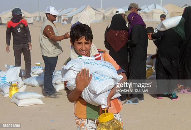 A displaced Iraqi boy from the embattled city of Fallujah carries bags of food provided by the World Food Programme at a camp where families are...