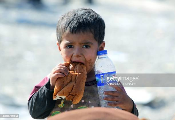 Displaced Iraqi boy from the Yazidi community eats a piece of bread and holds a bottle of water as they cross the Iraqi-Syrian border at the...
