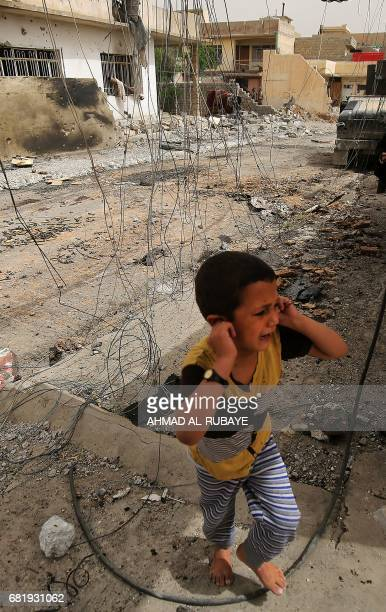 A displaced Iraqi boy from western Mosul's alIslah alZaraye neighbourhood reacts as he flees his home on May 11 2017 while government forces advance...