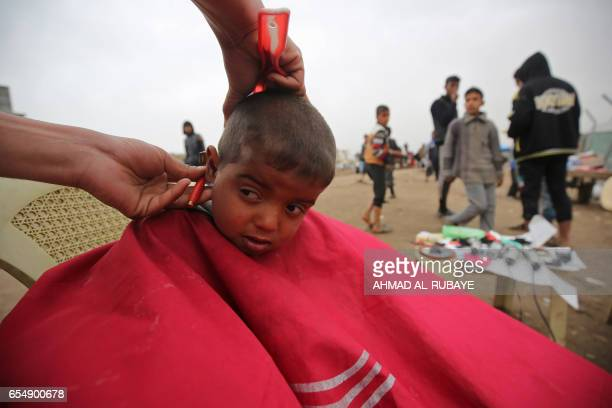 TOPSHOT A displaced Iraqi boy has a hair cut at the Hamam alAlil camp where many residents from Mosul are taking shelter as the government forces...