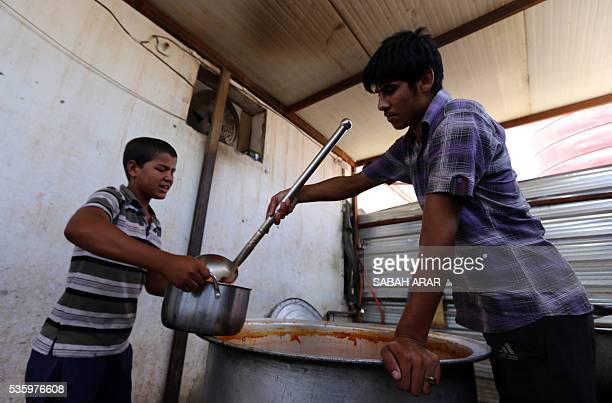 A displaced Iraqi boy who fled fighting between government forces and the Islamic State group in Anbar province receives donated food at the...