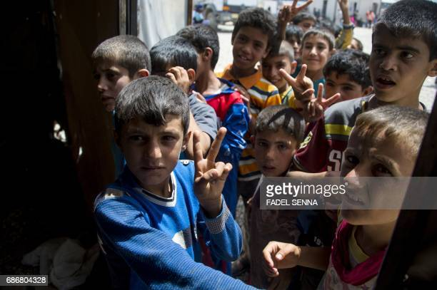 Displaced Iraqi boys flash the V-sign for victory upon their arrival at a camp for Internally Displaced People in Hammam al-Alil, south of Mosul,...