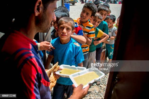 Displaced Iraqi boys queue to receive their meal upon their arrival at a camp for Internally Displaced People in Hammam alAlil south of Mosul after...