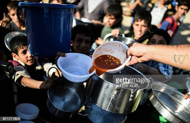 Displaced Iraqi boys wait to receive food at a refugee camp in the Khazir Region between Arbil and Mosul on November 5 2016 Aid workers have warned...