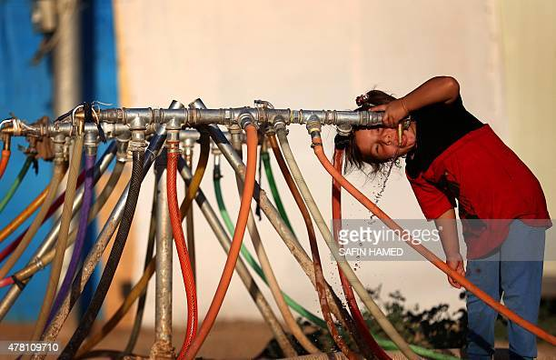 A displaced Iraqi child who fled her home due to attacks by the Islamic State group drinks water at the Harsham refugee camp where she found shelter...