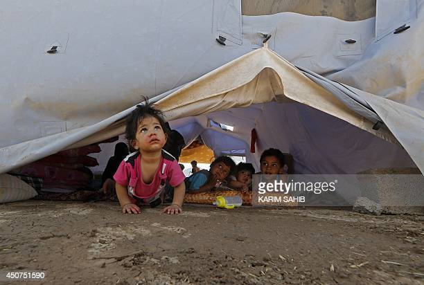 Displaced Iraqi children sit inside a UNHCR tent at a temporary camp set up to shelter people fleeing violence in northern Iraq on June 17 2014 in...