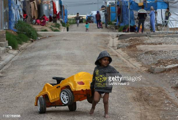 Displaced Iraqi children who fled their homes along with their families due to attacks by the Islamic State group play at the Harsham refugee camp...