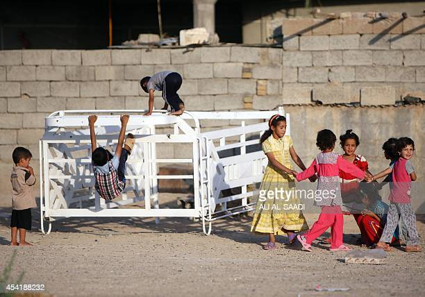 Displaced Iraqi children who fled Wadi Osaj village near Jalawla as battles between peshmerga and Islamic State jihadists broke out play as they take...