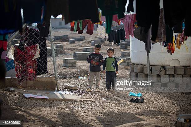 Displaced Iraqi children, who were forced to flee their home because of Islamic State's advance earlier this year, stand in front of tents that have...