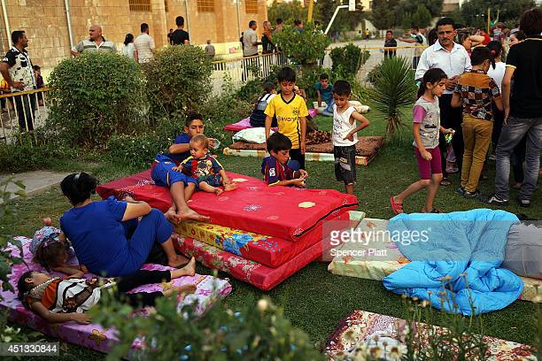 Displaced Iraqi Christians sleep in the courtyard of Saint Joseph's church after having to flee their district on June 26 2014 in Erbil IraqTens of...