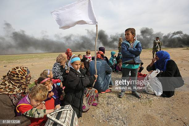 Displaced Iraqi families gather as they flee a military operation by Iraqi security personnel aimed at retaking areas from Islamic State group...