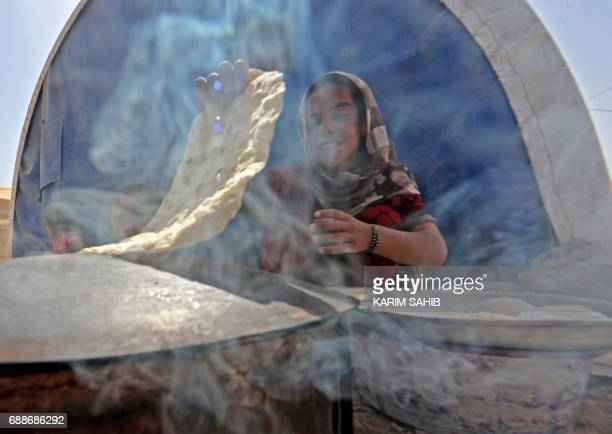 Displaced Iraqi girl bakes bread at the Hammam al-Alil camp for internally displaced people south of Mosul on May 26 as government forces continue...
