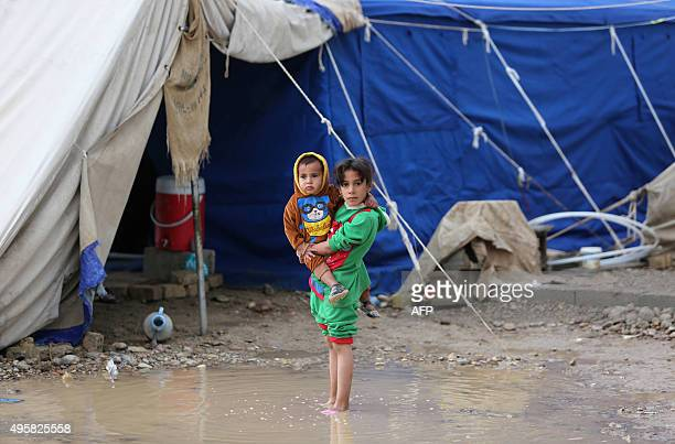 A displaced Iraqi girl carries her brother in flooded water at a camp in Baghdad following heavy rainfall on November 5 2015 Torrential rain caused...