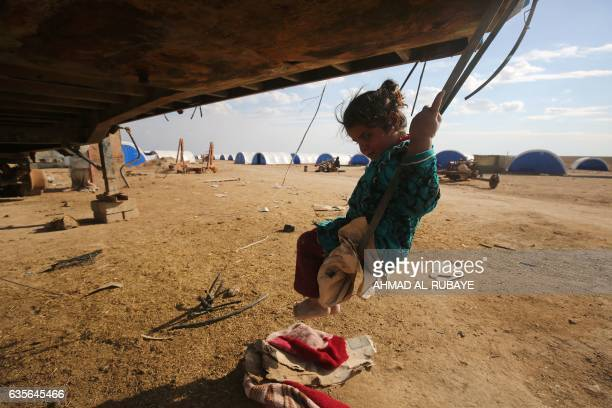 TOPSHOT A displaced Iraqi girl plays on a swing at the AlAgha camp where Iraqi families from the nearby villages of Tal Afar southwest of Mosul are...