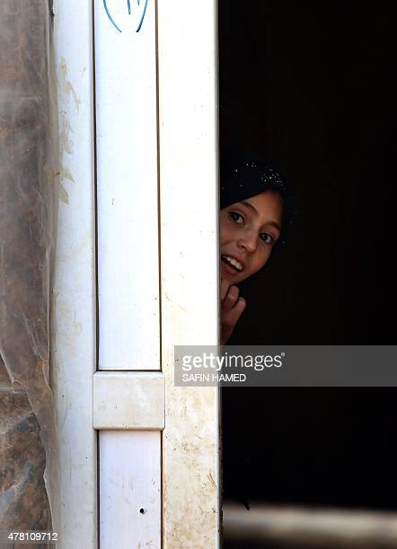 A displaced Iraqi girl who fled her home due to attacks by the Islamic State group looks out from behind a door at the Harsham refugee camp where she...
