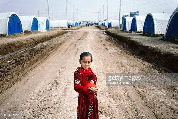 TOPSHOT A displaced Iraqi girl who fled the violence in the Islamic State group stronghold of Mosul holds a balloon at the Khazer refugee camp for...