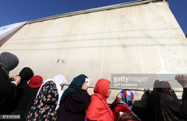 TOPSHOT Displaced Iraqi Kurds who fled their homes due to the violence gather to receive humanitarian winter aid supplied by the French government on...