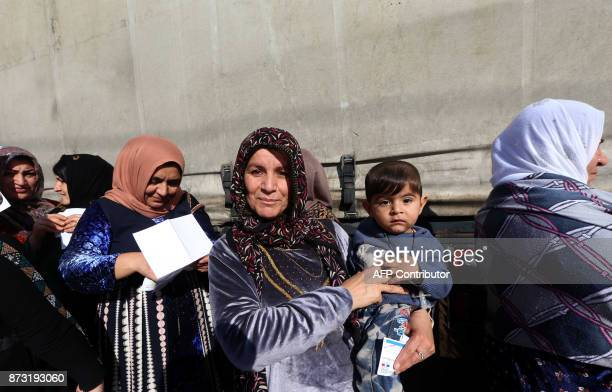 Displaced Iraqi Kurds who fled their homes due to the violence gather to receive humanitarian winter aid supplied by the French government on...