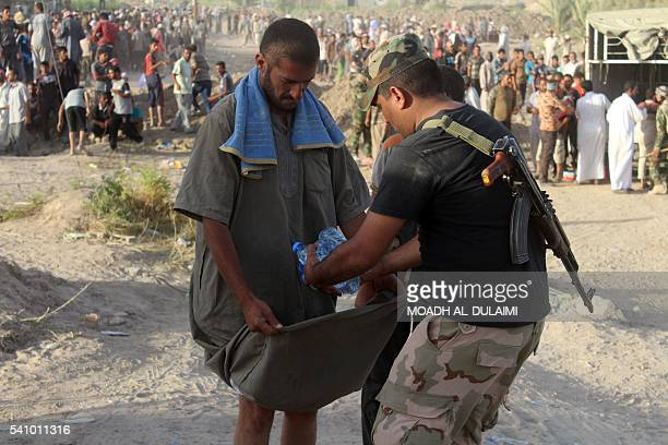 A displaced Iraqi man receives bottles of water upon his arrival at a safe zone on June 17 2016 in Amriyat alFallujah after Iraqi government forces...
