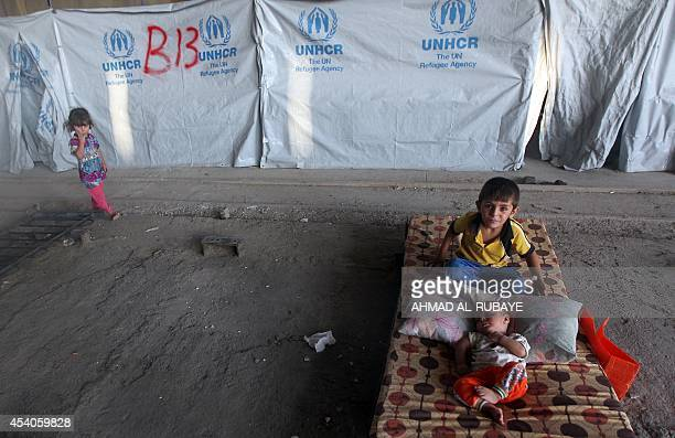 Displaced Iraqi Shiite children who fled their homes a few weeks ago due to attacks by Islamic State jihadists in the northern city of Mosul rest...
