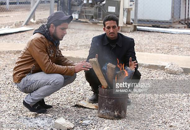 Displaced Iraqi Turkmen refugees warm up around a firecamp at the Nabi Yunes refugee camp near the Iraqi capital Baghdad on January 11 2015 Iraq's...