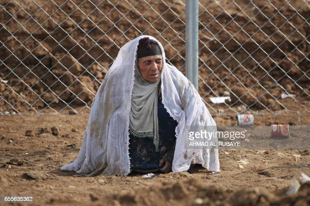TOPSHOT A displaced Iraqi woman from Mosul waits upon her arrival at the Hamam alAlil camp on March 20 during the government forces ongoing offensive...