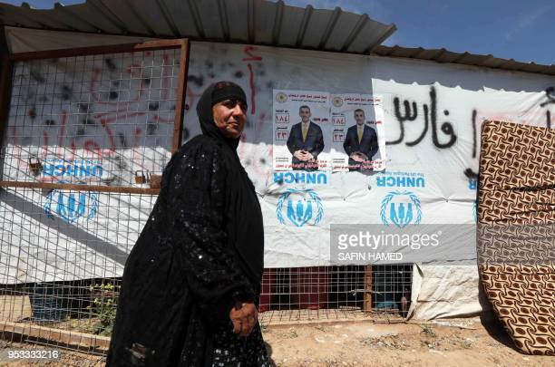 TOPSHOT A displaced Iraqi woman from the former embattled city of Mosul walks past an election campaign poster at the Hasan Sham camp some 40...