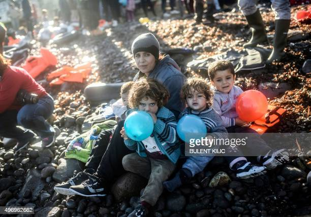 A displaced Iraqi woman from the Yazidi community who fled violence from Islamic State group jihadists sits with her children holding blue and red...