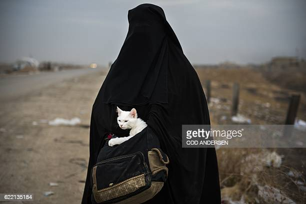 A displaced Iraqi woman holds her cat Lulu as she waits for transport in the Iraqi Kurdish checkpoint village of Shaqouli about 35 kilometres east of...