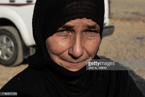 Displaced Iraqi woman prepares to board a bus at a camp for displaced people in Hammam al-Alil, south of the northern Iraqi city of Mosul, on August...
